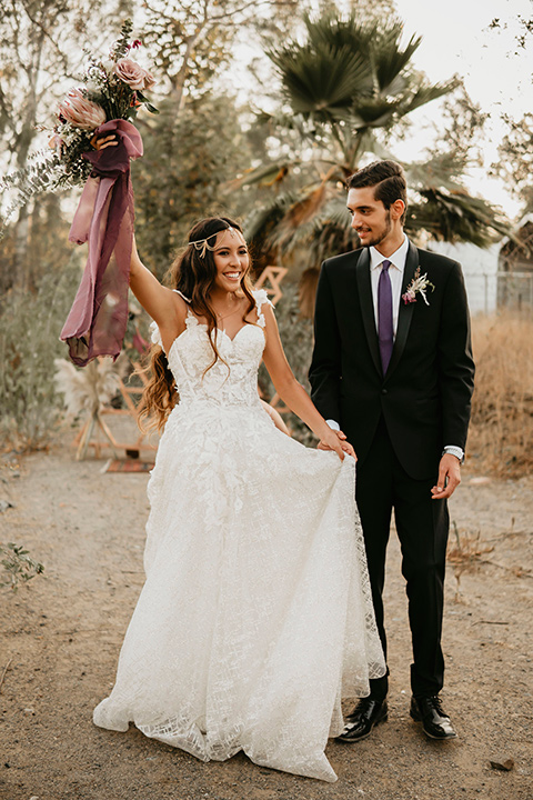 boho elopement shoot with the bride in a lace ball gown and a gold chair headpiece and the groom in a black suit with a long black tie walking away from ceremony