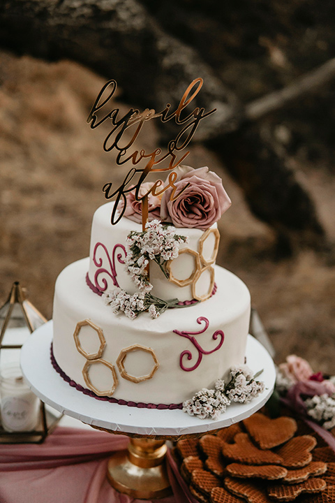 two tiered cake with white icing and blush toned decor