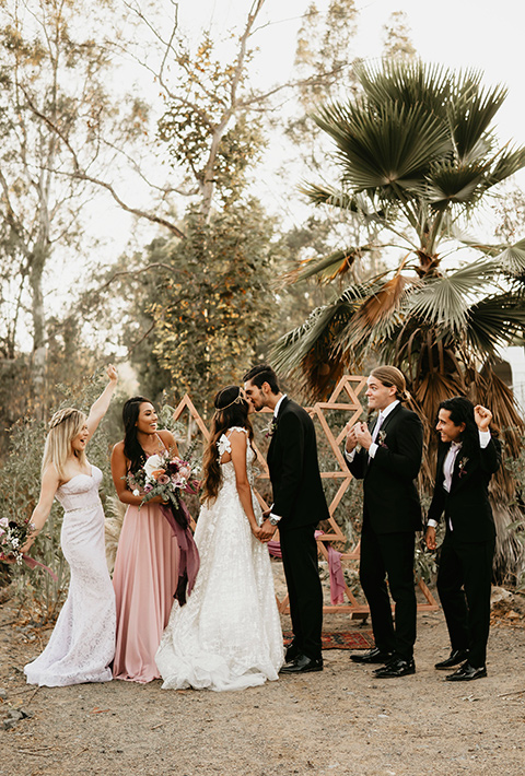 bride in an ivory lace gown with a gold chain headpiece and the groom in a black suit with a black long tie and the bridesmaids in pink dresses with the groomsmen in black suits and black ties