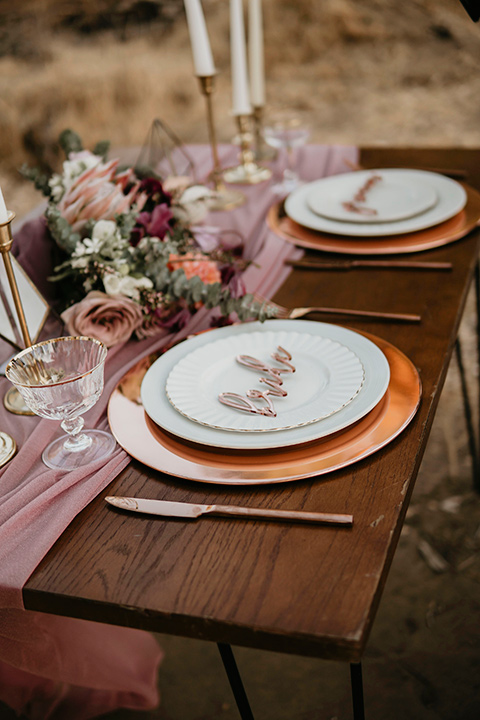 wooden tables with pink aisle runners with gold chargers and white plates