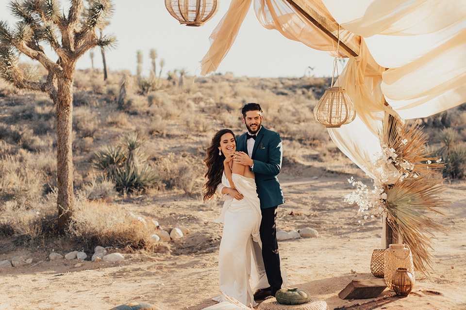 Bride and groom pose for a photo with the desert in the background