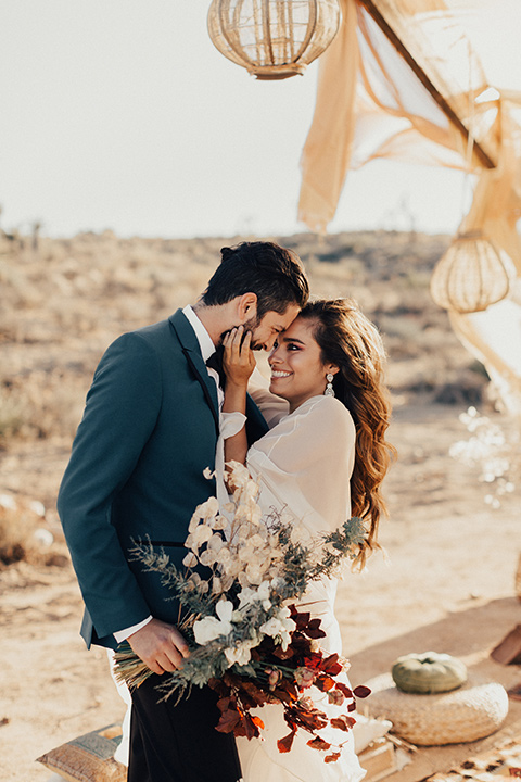 A bride and groom embrace each other for a wedding photo in the desert