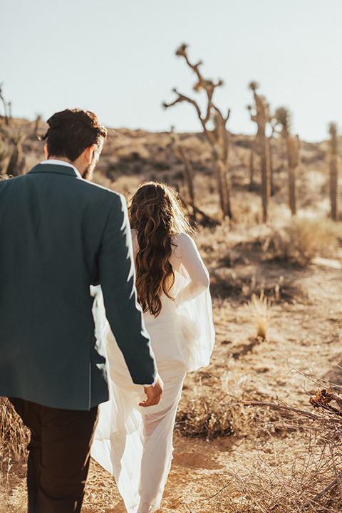 Photo from behind of the bride and groom walking in the desert