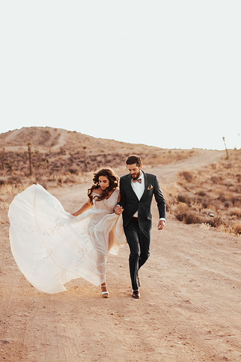 Bride and groom run in the desert