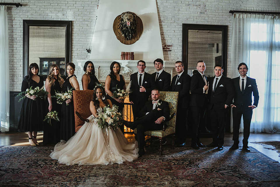 The-Ebell-In-Long-Beach-Wedding-bridalparty-bridesmaids-in-black-dresses-groomsmen-in-black-tuxeds-with-black-long-ties-bride-in-a-champagne-ballgown-with-a-strapless-neckline-and-the-groom-in-a-black-tuxedo-with-a-rose-gold-bow-tie