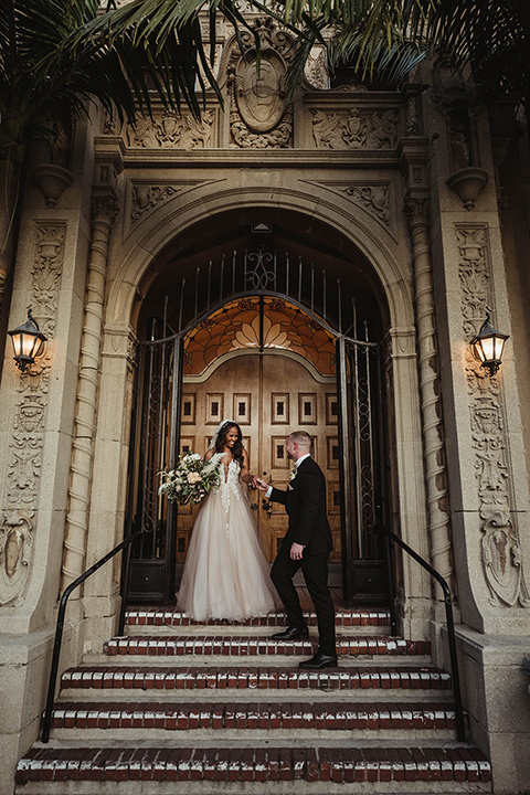 The-Ebell-In-Long-Beach-Wedding-bride-and-groom-by-steps-bride-in-a-champagne-ballgown-with-a-strapless-neckline-and-the-groom-in-a-black-tuxedo-with-a-rose-gold-bow-tie