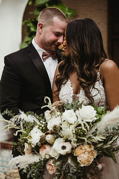 The-Ebell-In-Long-Beach-Wedding-bride-and-groom-close-bride-in-a-champagne-ballgown-with-a-strapless-neckline-and-the-groom-in-a-black-tuxedo-with-a-rose-gold-bow-tie