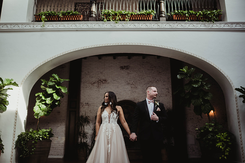 The-Ebell-In-Long-Beach-Wedding-bride-and-groom-looking-in-different-directions-bride-in-a-champagne-ballgown-with-a-strapless-neckline-and-the-groom-in-a-black-tuxedo-with-a-rose-gold-bow-tie