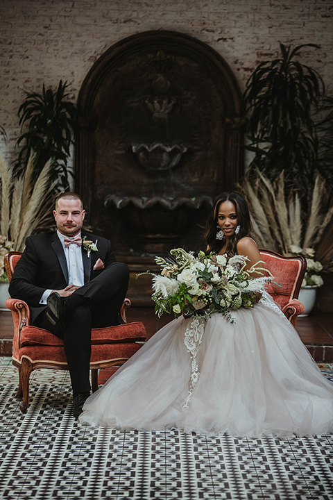 The-Ebell-In-Long-Beach-Wedding-bride-and-groom-sitting-bride-in-a-strapless-ballgown-and-groom-in-a-black-tuxedo-with-a-rose-gold-bow-tie