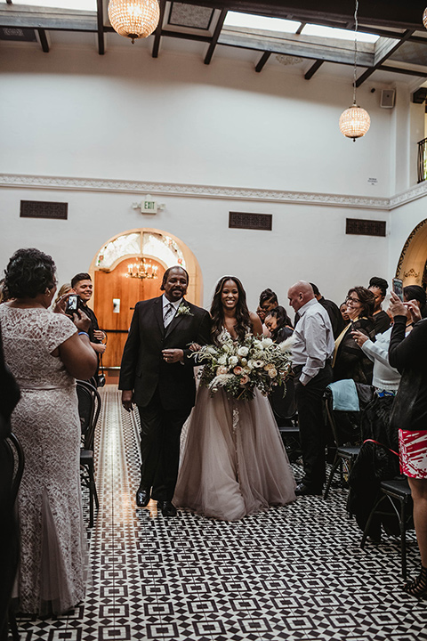 The-Ebell-In-Long-Beach-Wedding-bride-walking-down-the-aisle-bride-in-a-champagne-ballgown-with-a-strapless-neckline-and-the-groom-in-a-black-tuxedo-with-a-rose-gold-bow-tie