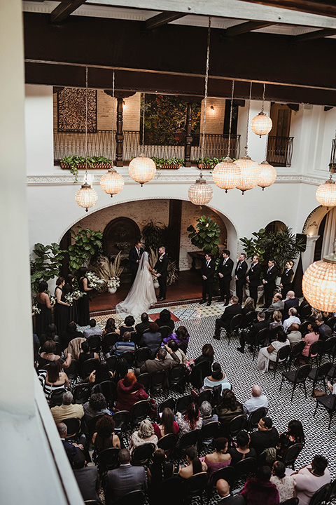 The-Ebell-In-Long-Beach-Wedding-ceremony-view-bride-in-a-strapless-ballgown-and-groom-in-a-black-tuxedo-with-a-rose-gold-bow-tie