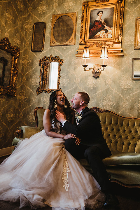 The-Ebell-In-Long-Beach-Wedding-couple-sitting-inside-bride-sitting-bride-in-a-strapless-ballgown-and-groom-in-a-black-tuxedo-with-a-rose-gold-bow-tie