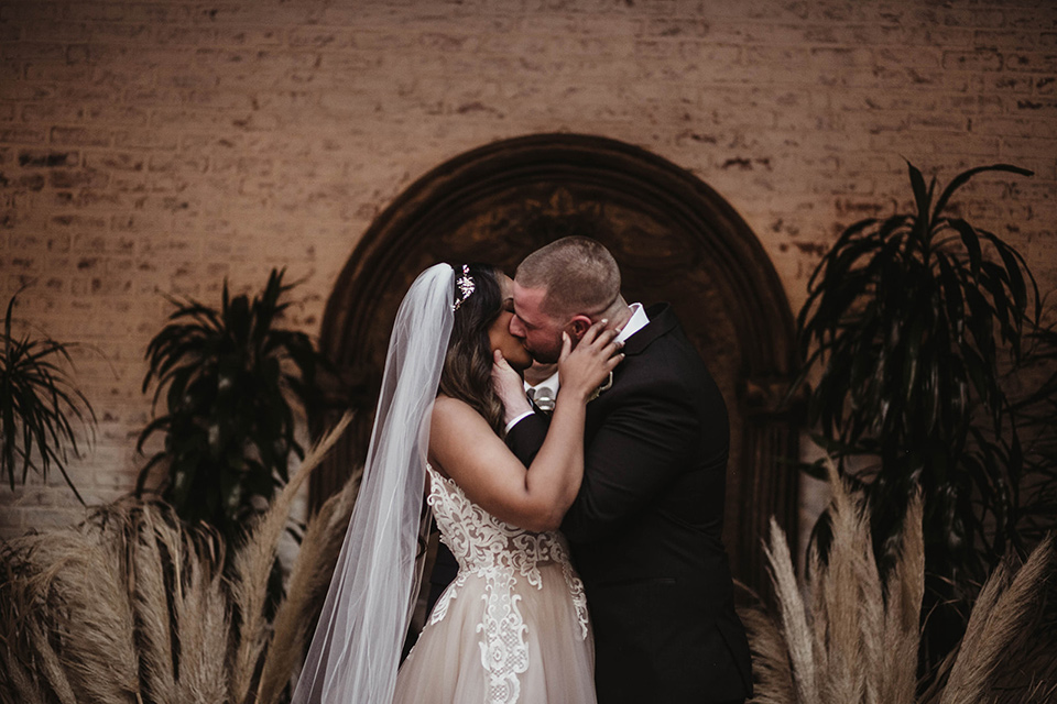 The-Ebell-In-Long-Beach-Wedding-first-kiss-bride-in-a-champagne-ballgown-with-a-strapless-neckline-and-the-groom-in-a-black-tuxedo-with-a-rose-gold-bow-tie