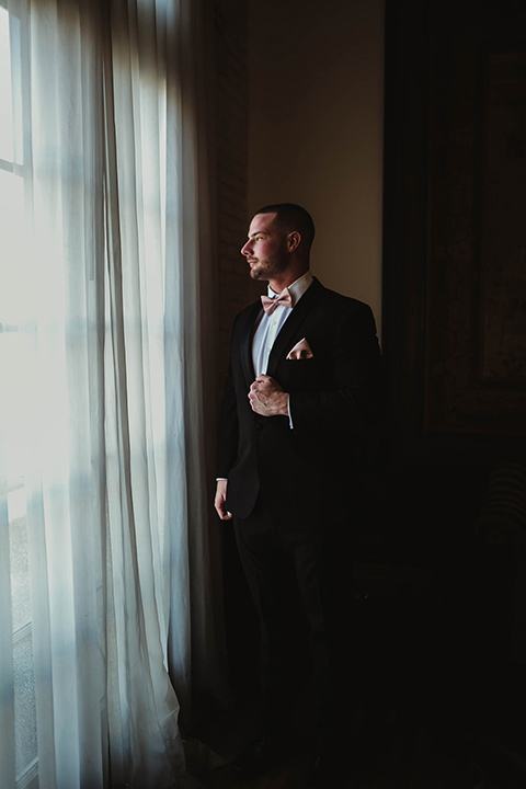 The-Ebell-In-Long-Beach-Wedding-groom-looking-out-the-window-in-a-black-tuxedo-with-a-rose-gold-bow-tie