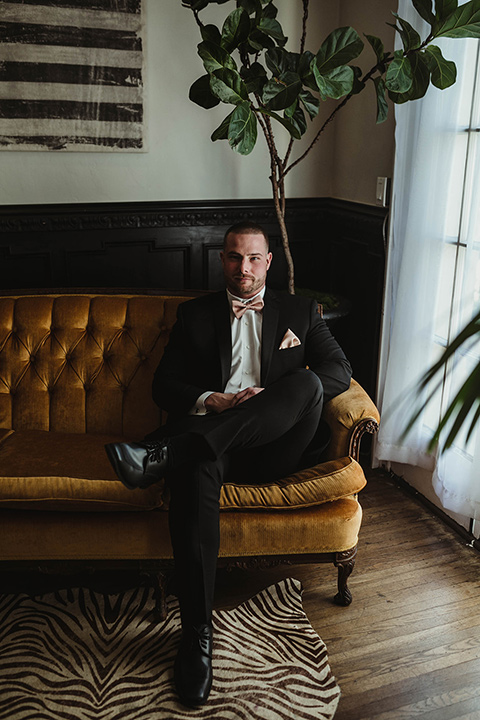 The-Ebell-In-Long-Beach-Wedding-groom-sitting-in-a-black-tuxedo-with-a-rose-gold-bow-tie