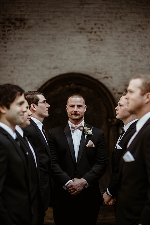 The-Ebell-In-Long-Beach-Wedding-group-groomsmen-photo-everyone-in-black-tuxedos-with-black-long-ties-and-groom-in-a-rose-gold-bow-tie