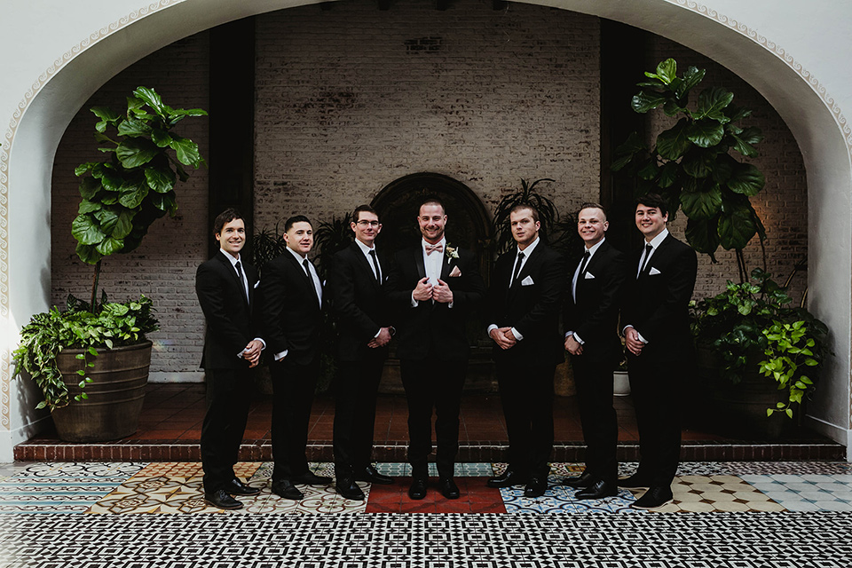 The-Ebell-In-Long-Beach-Wedding-groomsmen-groom-in-a-black-tuxedo-with-a-rose-gold-bow-tie-groomsmen-in-black-tuxedos-with-black-long-ties