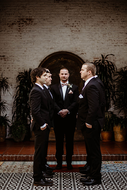 The-Ebell-In-Long-Beach-Wedding-groomsmen-standing-facing-each-other-groom-in-the-middle-close-up-groom-in-a-black-tuxedo-with-a-rose-gold-bow-tie-groomsmen-in-black-tuxedos-with-black-long-ties