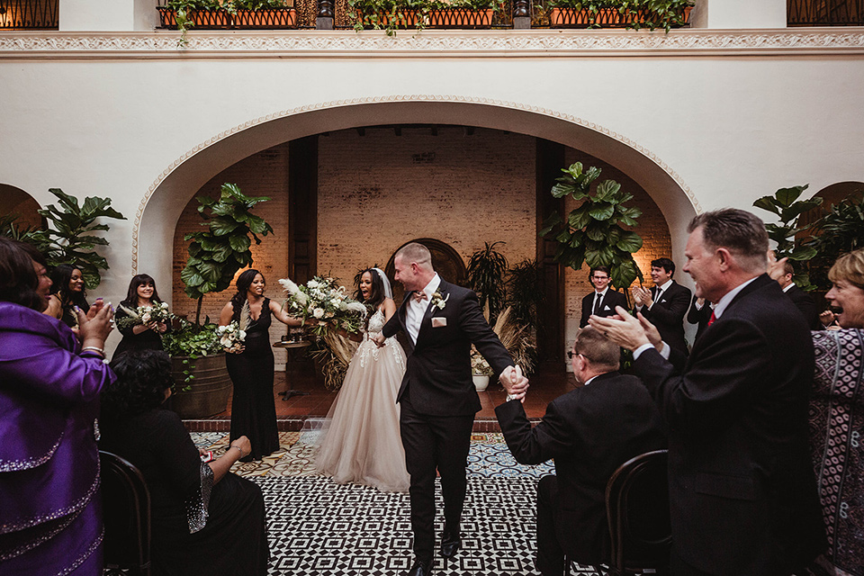 The-Ebell-In-Long-Beach-Wedding-walking-down-the-aisle-bride-in-a-champagne-ballgown-with-a-strapless-neckline-and-the-groom-in-a-black-tuxedo-with-a-rose-gold-bow-tie