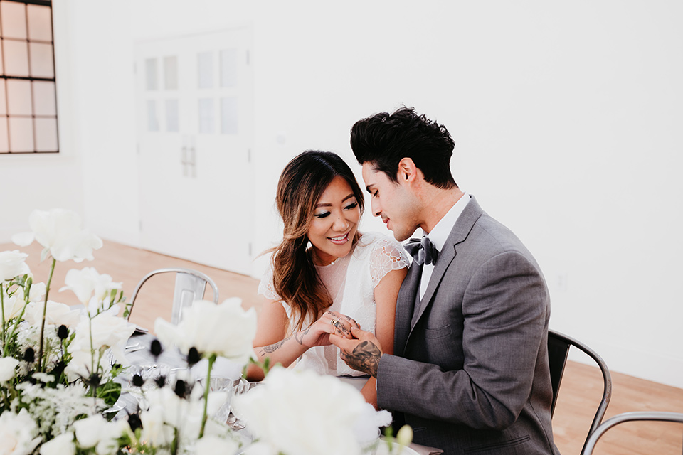 Building-177-Styled-Shoot-bride-and-groom-at-table-bride-in-a-flowing-white-gown-with-short-sleeves-and-beading-detail-groom-in-a-grey-suit-with-a-grey-velvet-bow-tie