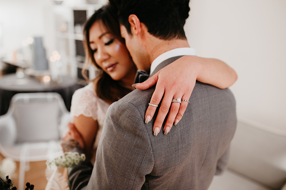 Building-177-Styled-Shoot-bride-and-groom-embrace-bride-in-a-flowing-white-gown-with-short-sleeves-and-beading-detail-groom-in-a-grey-suit-with-a-grey-velvet-bow-tie