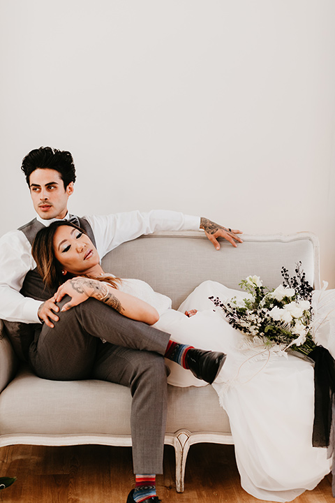 Building-177-Styled-Shoot-bride-and-groom-laying-on-couch-bride-in-a-flowing-white-gown-with-short-sleeves-and-beading-detail-groom-in-a-grey-suit-with-a-grey-velvet-bow-tie