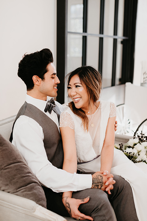 Building-177-Styled-Shoot-bride-and-groom-sitting-on-couch-bride-in-a-flowing-white-gown-with-short-sleeves-and-beading-detail-groom-in-a-grey-suit-with-a-grey-velvet-bow-tie