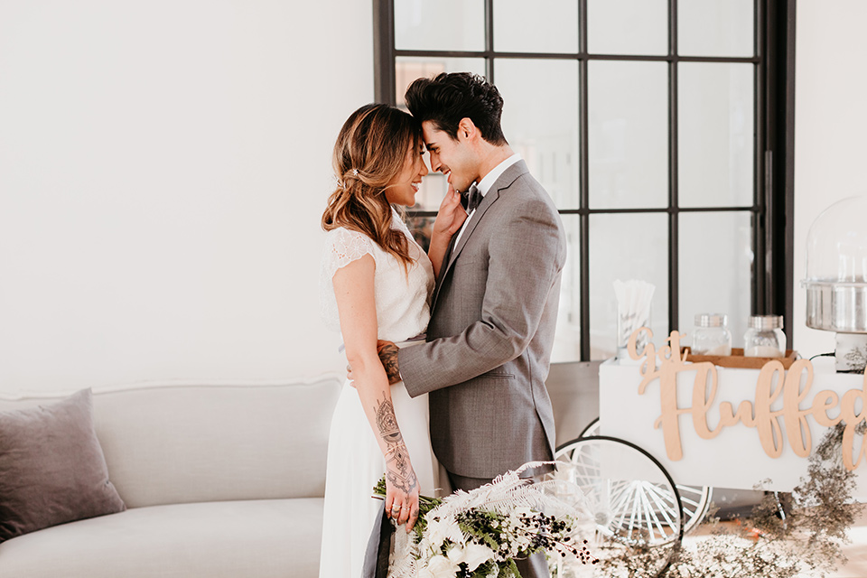 Building-177-Styled-Shoot-bride-and-groom-touching-heads-bride-in-a-flowing-white-gown-with-short-sleeves-and-beading-detail-groom-in-a-grey-suit-with-a-grey-velvet-bow-tie