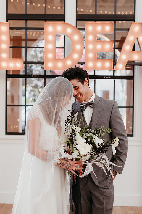 Building-177-Styled-Shoot-bride-with-veil-at-ceremony-with-groom-bride-in-a-flowing-white-gown-with-short-sleeves-and-beading-detail-groom-in-a-grey-suit-with-a-grey-velvet-bow-tie