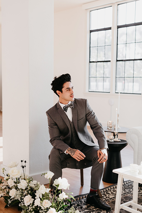 Building-177-Styled-Shoot-groom-by-window-in-a-grey-suit-with-a-grey-velvet-bow-tie