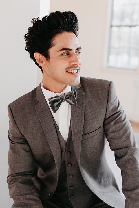 Building-177-Styled-Shoot-groom-looking-away-from-camera-in-a-grey-suit-with-a-grey-velvet-bow-tie