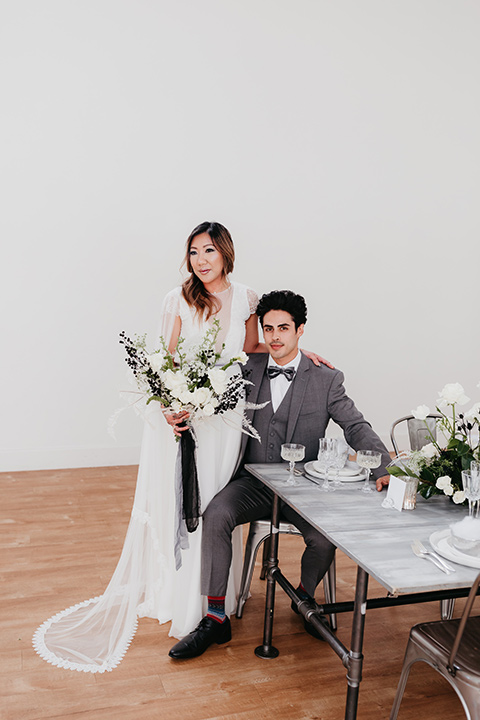 Building-177-Styled-Shoot-groom-sitting-and-bride-standing-by-table-bride-in-a-flowing-white-gown-with-short-sleeves-and-beading-detail-groom-in-a-grey-suit-with-a-grey-velvet-bow-tie