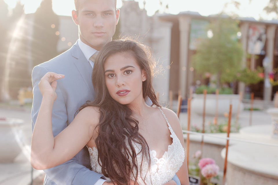 California Dreaming Shoot bride and groom looking at the camera bride in a lace form fitting gown with thin straps groom in a light blue suit
