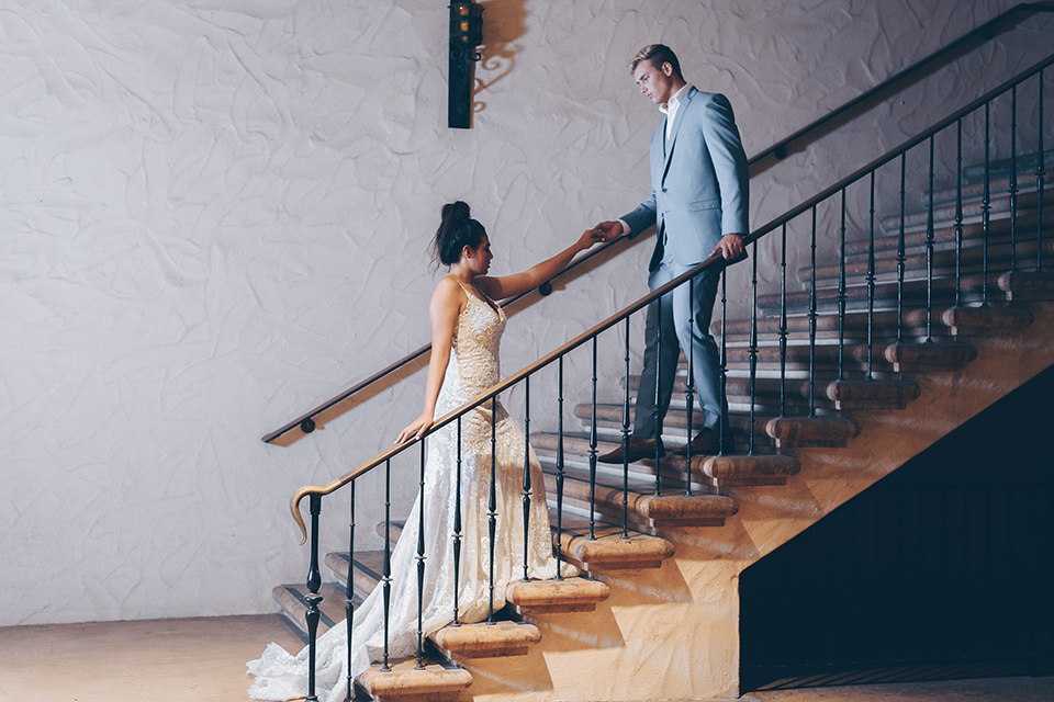 bride and groom on steps bride in a lace form fitting gown with thin straps groom in a light blue suit