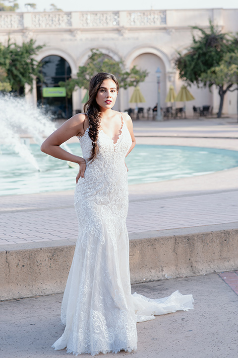 bride by fountain in a form-fitting lace gown with thin straps