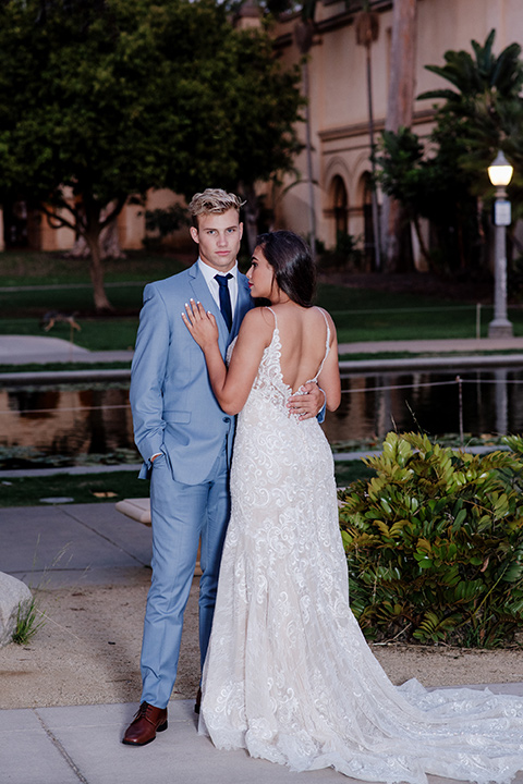 California Dreaming Shoot groom facing camera bride facing groom bride in a form fitting lace gown with thin straps groom in a light blue suit