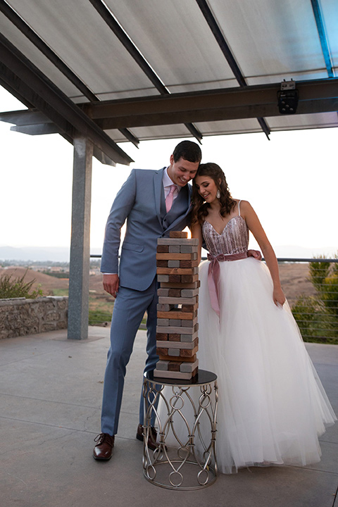 Callaway-Styled-Shoot-bride-and-groom-playing-jenga-bride-in-a-tulle-ballgown-with-a-colorful-beaded-bodice-groom-in-a-light-blue-suit