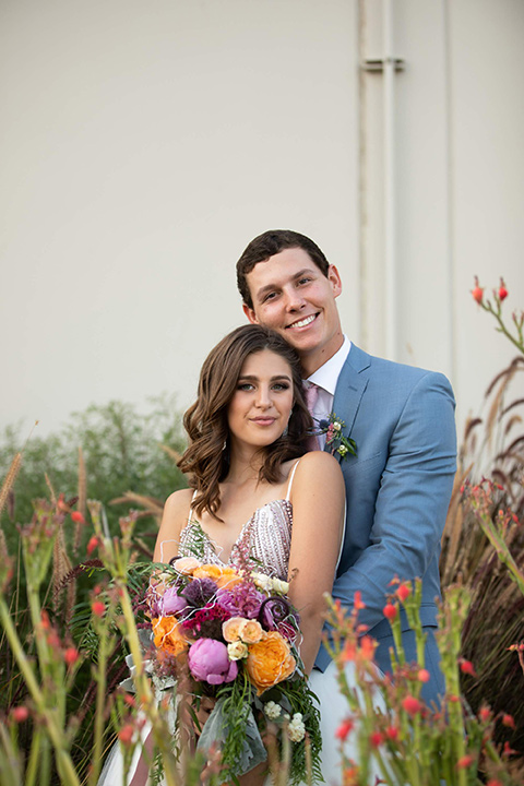 Callaway-Styled-Shoot-bride-and-groom-smiling-at-camera-bride-in-a-tulle-ballgown-with-a-colorful-beaded-bodice-groom-in-a-light-blue-suit