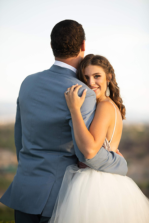 Callaway-Styled-Shoot-bride-looking-at-camera-groom-back-towards-camera-bride-in-a-tulle-ballgown-with-a-colorful-beaded-bodice-groom-in-a-light-blue-suit