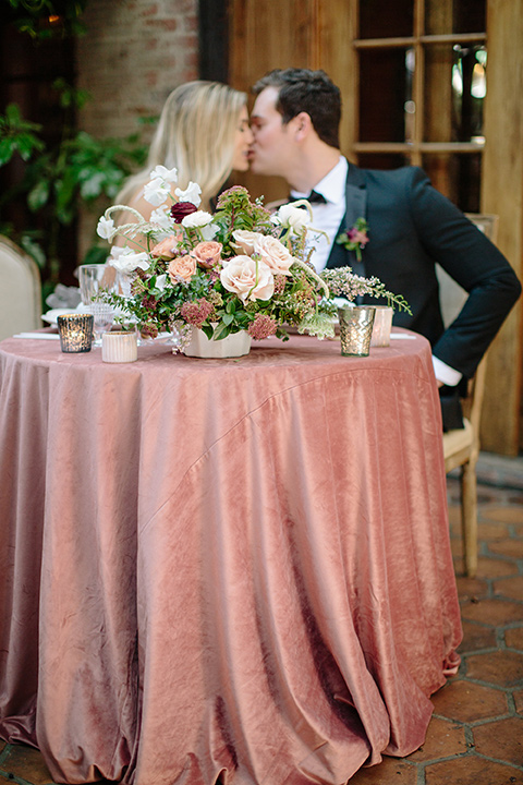 Carondelet-House-wedding-bride-and-groom-at-sweetheart-table-bride-and-groom-at-bride-in-a-lace-gown-with-an-illusion-neckline-and-thin-straps-groom-in-a-traditional-black-tuxedo-with-a-black-bow-tie