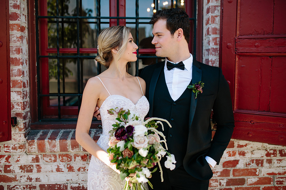 Carondelet-House-wedding-bride-and-groom-looking-at-each-other-bride-in-a-lace-gown-with-an-illusion-neckline-and-thin-straps-groom-in-a-traditional-black-tuxedo-with-a-black-bow-tie