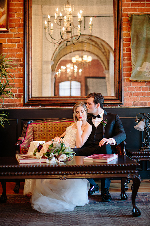 Carondelet-House-wedding-bride-and-groom-on-couch-bride-and-groom-at-bride-in-a-lace-gown-with-an-illusion-neckline-and-thin-straps-groom-in-a-traditional-black-tuxedo-with-a-black-bow-tie