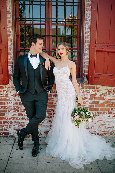 Carondelet-House-wedding-bride-and-groom-standing-facing-camera-bride-in-a-lace-gown-with-an-illusion-neckline-and-thin-straps-groom-in-a-traditional-black-tuxedo-with-a-black-bow-tie