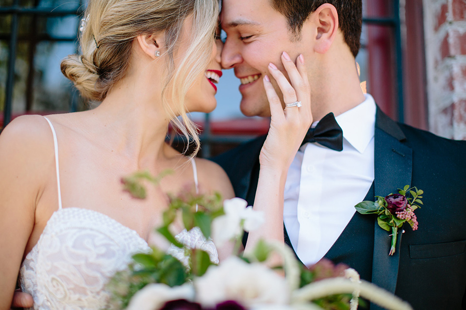 Carondelet-House-wedding-bride-and-groom-touching-heads-bride-in-a-lace-gown-with-an-illusion-neckline-and-thin-straps-groom-in-a-traditional-black-tuxedo-with-a-black-bow-tie