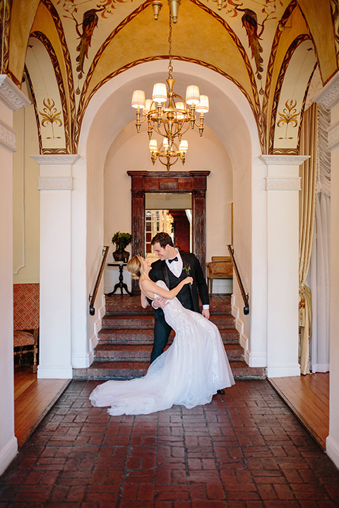 Carondelet-House-wedding-groom-dipping-bride-at-bride-in-a-lace-gown-with-an-illusion-neckline-and-thin-straps-groom-in-a-traditional-black-tuxedo-with-a-black-bow-tie