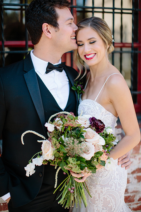 Carondelet-House-wedding-groom-kissing-bride-on-forehead-bride-in-a-lace-gown-with-an-illusion-neckline-and-thin-straps-groom-in-a-traditional-black-tuxedo-with-a-black-bow-tie