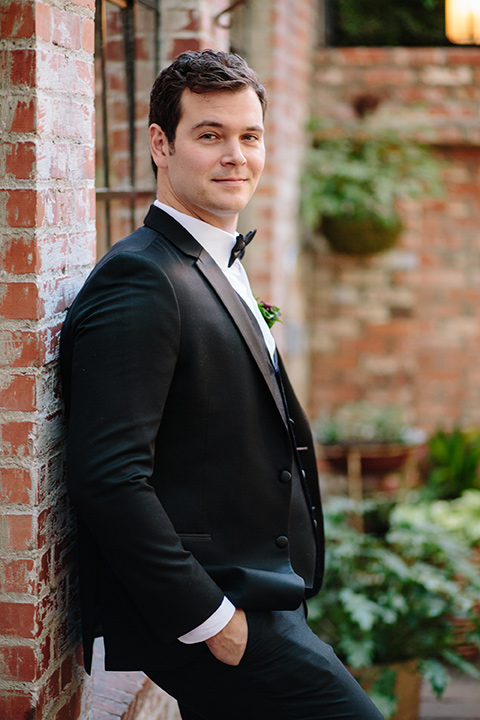Carondelet-House-wedding-groom-leaning-on-wall-in-a-traditional-black-tuxedo-with-a-black-bow-tie