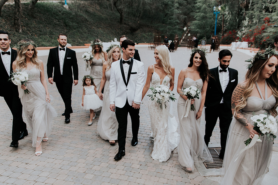 rancho-las-lomas-real-wedding-bridalparty-walking-the-bridesmaids-in-nude-and-taupe-long-gowns-the-groomsmen-in-black-tuxedos-with-black-bow-ties-the-bride-is-in-a-lace-long-gown-with-a-deep-v-and-straps-and-the-groom-is-in-a-white-shawl-lapel-tuxedo-with-black-pants-and-a-black-bow-tie