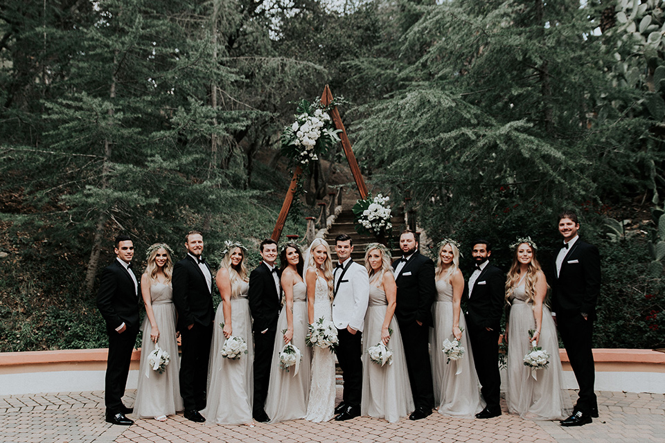 rancho-las-lomas-real-wedding-bridalparty-the-bridesmaids-in-nude-and-taupe-long-gowns-the-groomsmen-in-black-tuxedos-with-black-bow-ties-the-bride-is-in-a-lace-long-gown-with-a-deep-v-and-straps-and-the-groom-is-in-a-white-shawl-lapel-tuxedo-with-black-pants-and-a-black-bow-tie