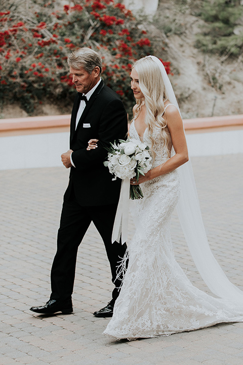 rancho-las-lomas-real-wedding-bride-and-father-thefather-in-a-black-nothc-lapel-tuxedo-the-bride-is-in-a-white-lace-formfitting-gown-with-straps